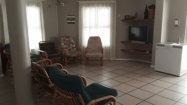 The spacious lounge at Tolbos. Comfortable chairs, with a refrigerator in the corder, and a television.